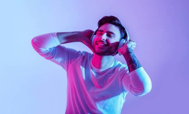 Relax with favorite music. Man in big wireless headphones closes eyes and enjoys song