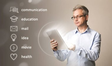 Mature man with tablet computer and user interface pictograms on virtual screen, grey background. Collage