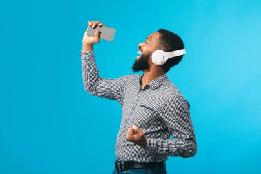 Afro man singing using smartphone as mic