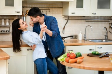 Young couple preparing dinner together at home, dancing