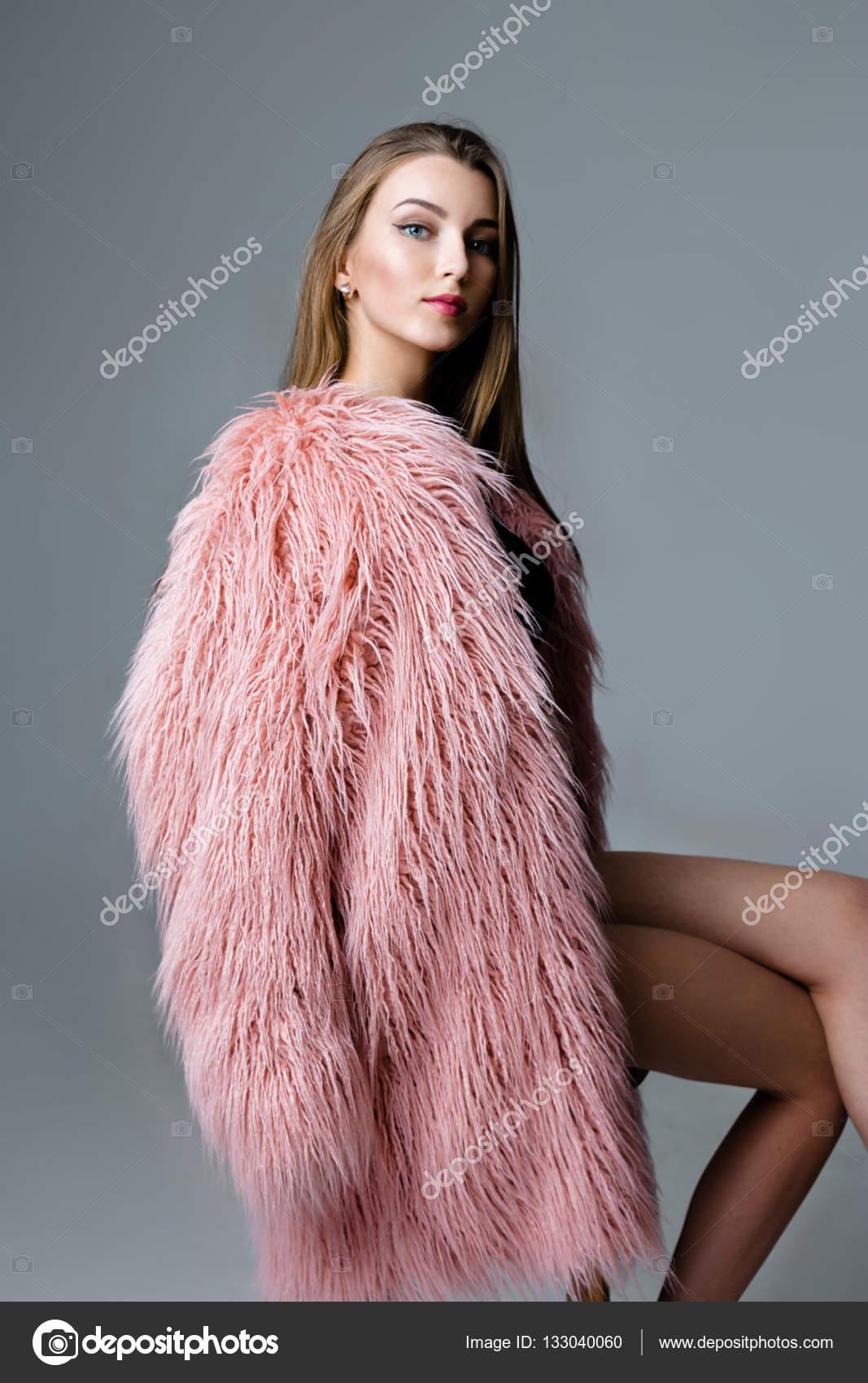 Πορτρέτο του όμορφη νεαρή γυναίκα σε ροζ γούνινο παλτό που θέτουν σε  στούντιο — Εικόνα από smmartynenko 89c6dbf76c1