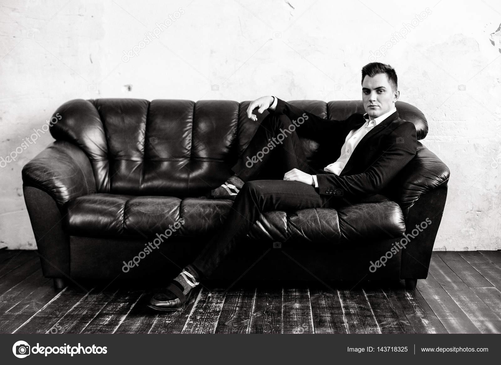 f64f46cb977b Μαύρο και άσπρο φωτογραφία του κομψό όμορφος νεαρός άνδρας στο λευκό  πουκάμισο και σακάκι ποζάρει στο δερμάτινο καναπέ — Εικόνα από ...