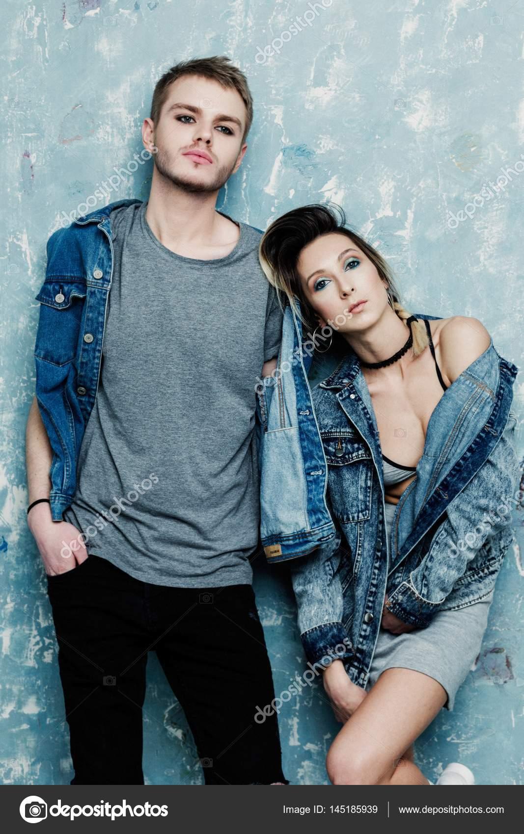 2ffd7d006143 Giovane coppia alla moda in abbigliamento casual che propone contro la  priorità bassa della parete di grunge — Foto di smmartynenko