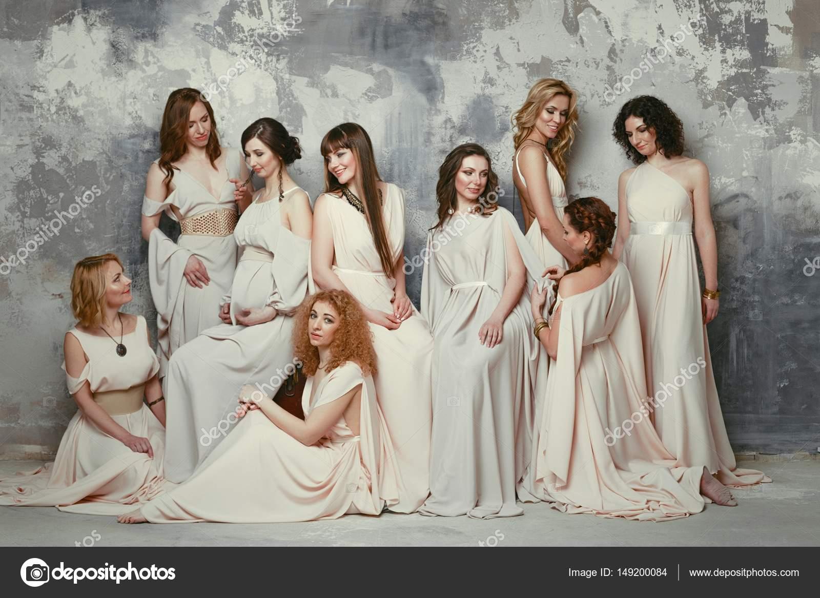 50a3b8804967 Nove belle giovani donne in posa in stile greco antico eleganti vestiti  lunghi contro priorità bassa della parete di grunge — Foto di smmartynenko