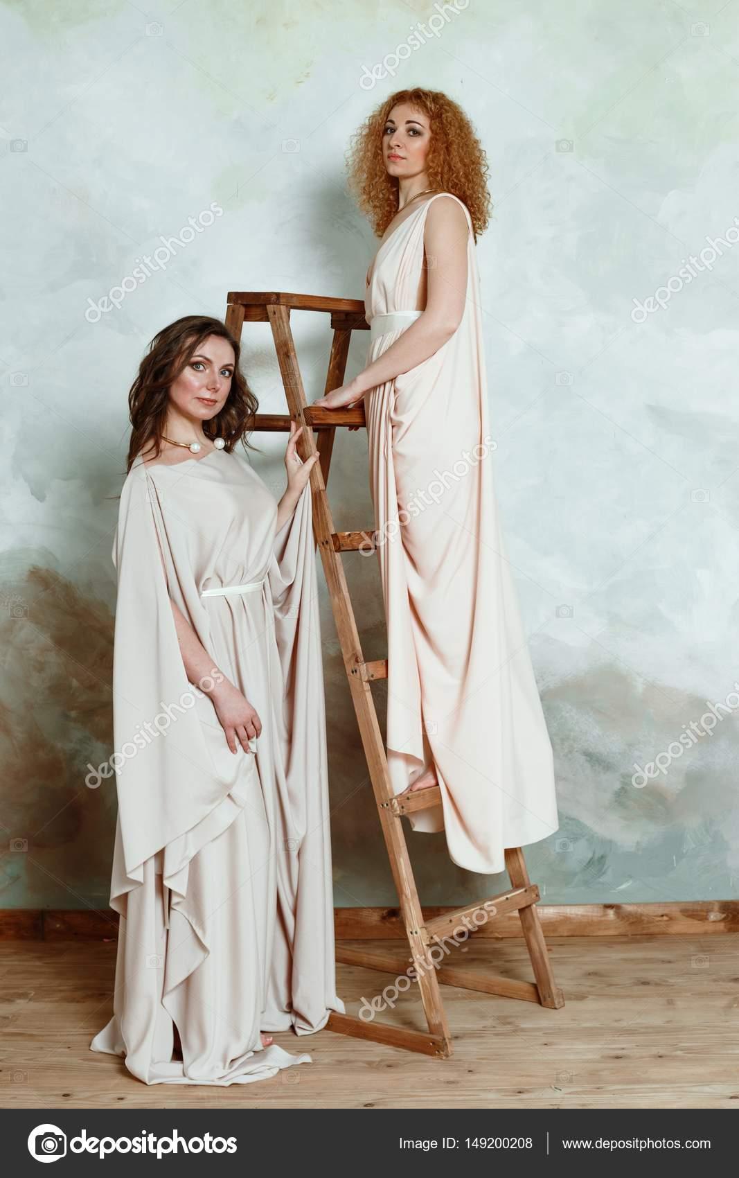 e5cce8d55806 Δύο όμορφες νεαρές γυναίκες ποζάρουν στο κομψό αρχαιοελληνικού τύπου μακριά  φορέματα τοίχος φόντο grunge — Εικόνα από ...