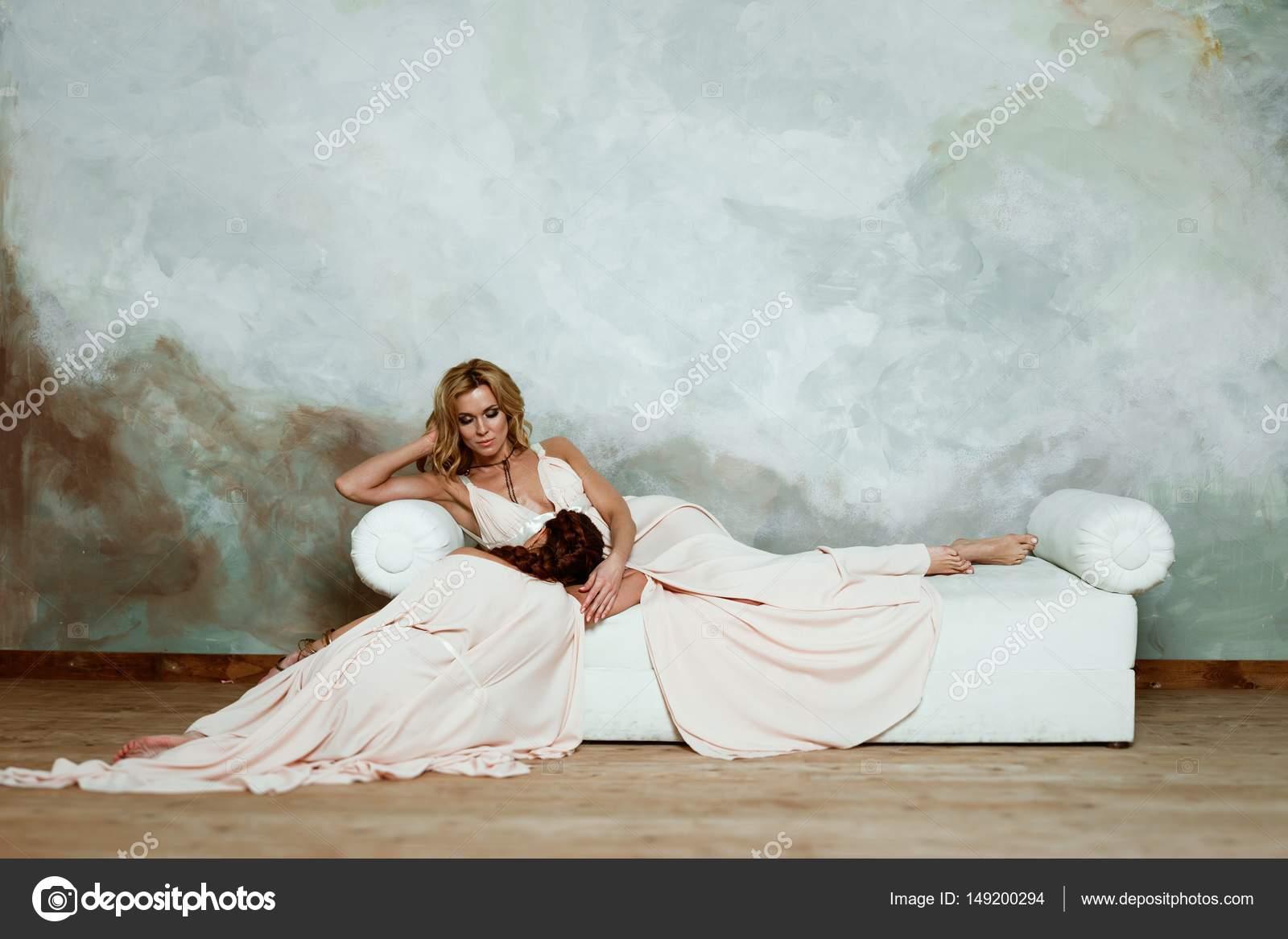 a957c00d13a Δύο όμορφες νεαρές γυναίκες ποζάρουν στο κομψό αρχαιοελληνικού τύπου μακριά  φορέματα τοίχος φόντο grunge — Εικόνα από ...