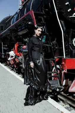 woman in vintage dress near steam locomotive