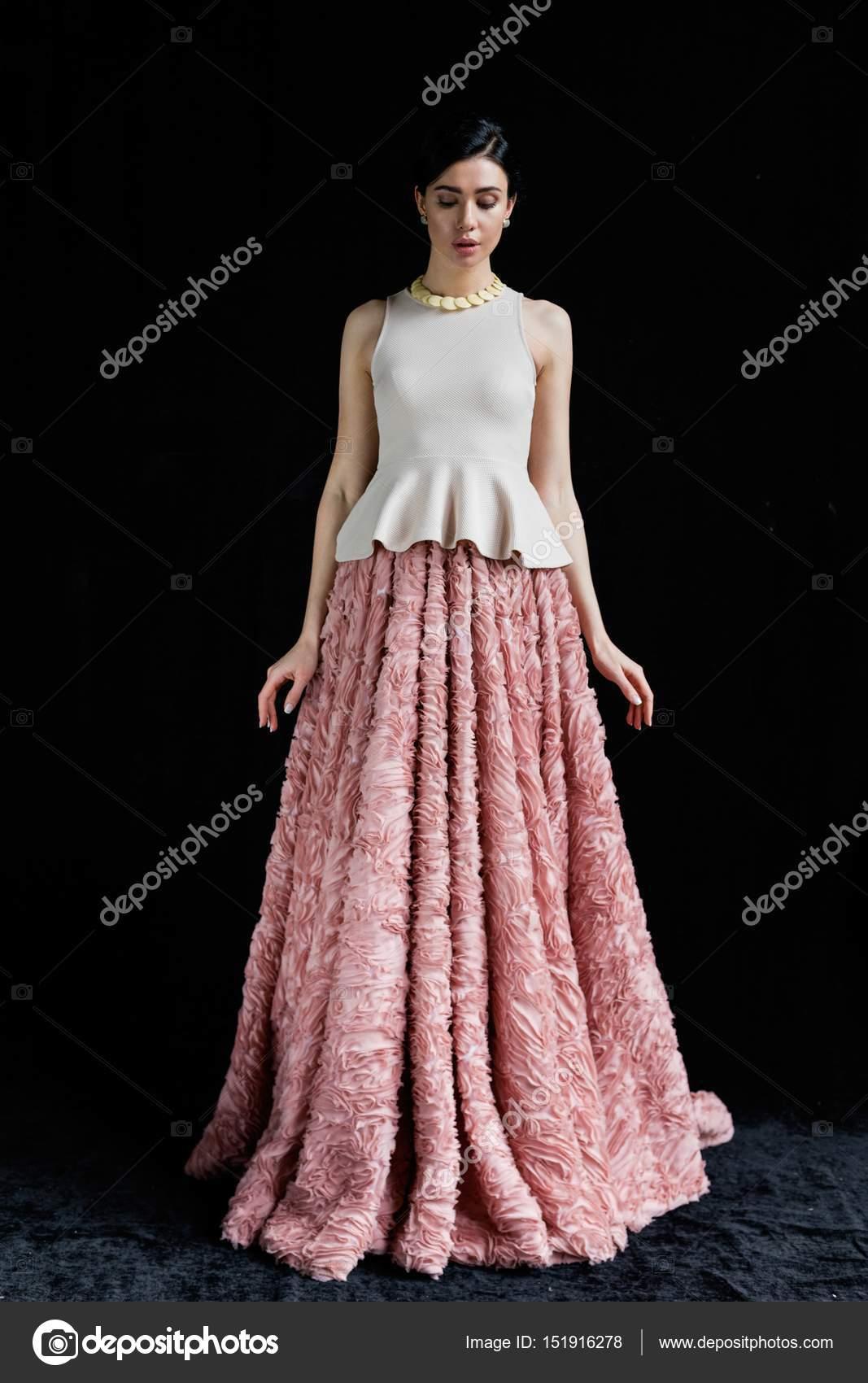 073e650a23e7 Giovane donna attraente in vestito rosa elegante che propone contro la  priorità bassa nera — Foto di smmartynenko