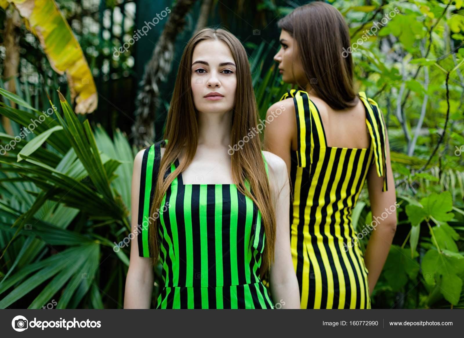 23095aefd42 Δύο νέοι όμορφες γυναίκες στον κομψό ριγέ φορέματα θέτοντας σε εξωτερικούς  χώρους — Εικόνα από smmartynenko