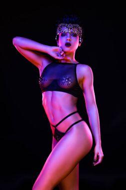 Sensual yound woman posing against dark studio background