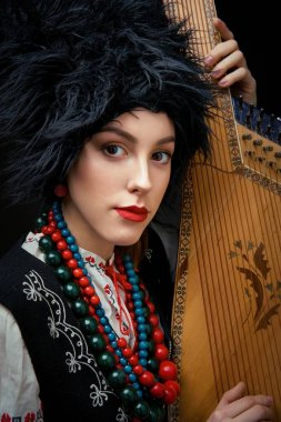 Portrait of gorgeouns young woman in ukrainian traditional costume holding bandura