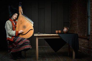 Gorgeouns young woman in ukrainian traditional costume with ukrainian musical instrument bandura