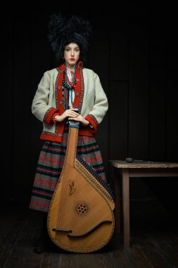 Gorgeouns young woman in ukrainian traditional costume with ukrainian musical instrument bandura