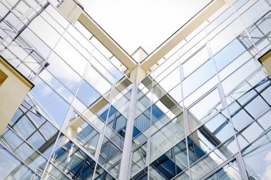 Facade of modern glass building with reflections of blue sky