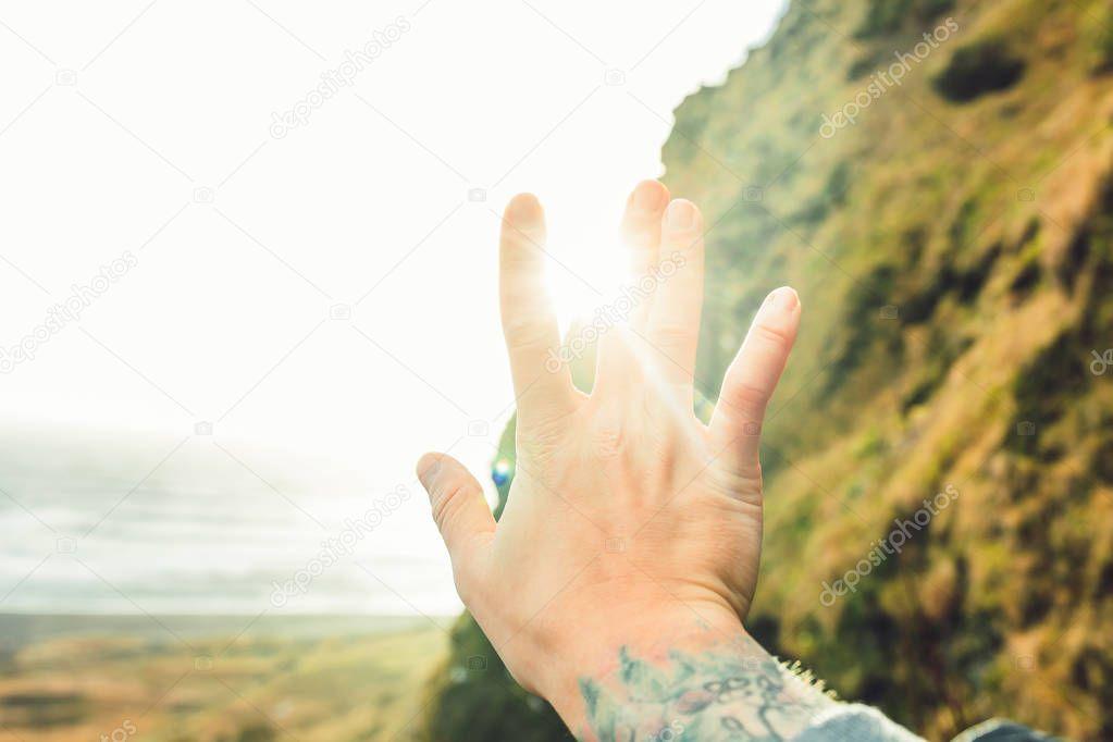 Hand raised over sunbeams