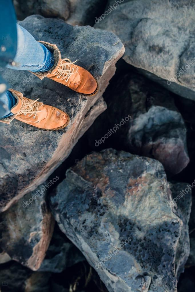 Legs in boots standing on stones