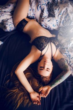 close-up of female body in black sexy lingerie on bed background