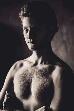 portrait of young shirtless handsome man on dark background, black and white