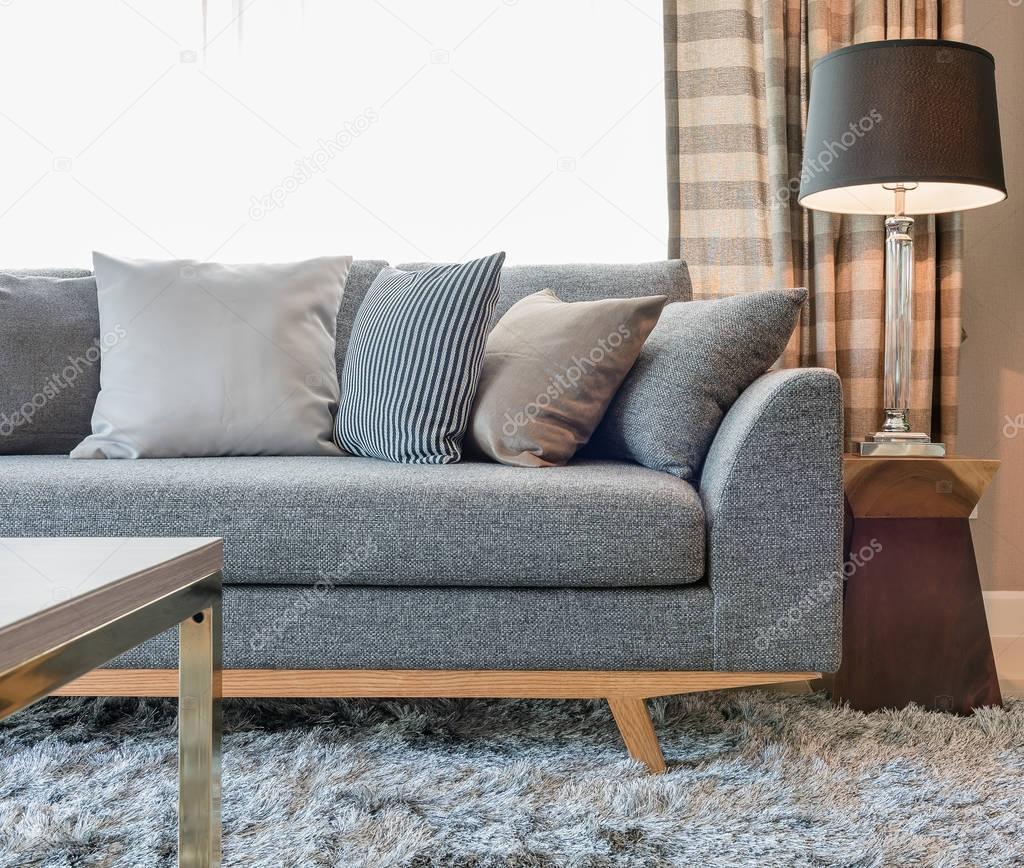 rij van kussens op grijze bank met zwarte lamp in woonkamer ...