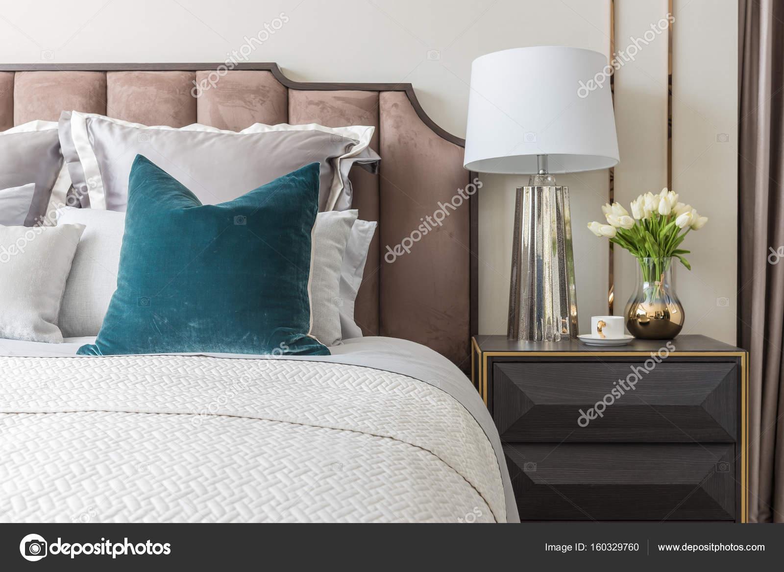 stile camera da letto classica con set di cuscini e lampada sul lato ...
