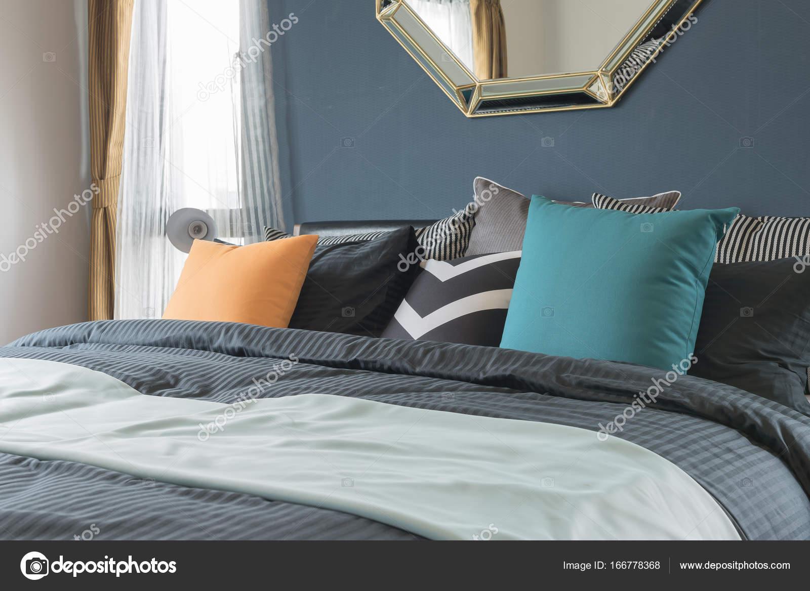 cuscini colorati su letto di colore scuro in camera da letto moderna ...
