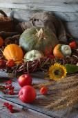 Autumn arrangement with decorative pumpkins, sunflowers, apples