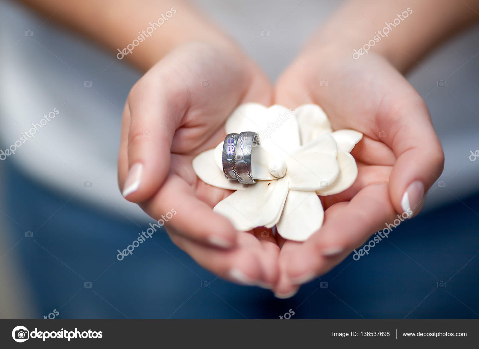 Female hands holding wedding rings placed on decorative flower ...