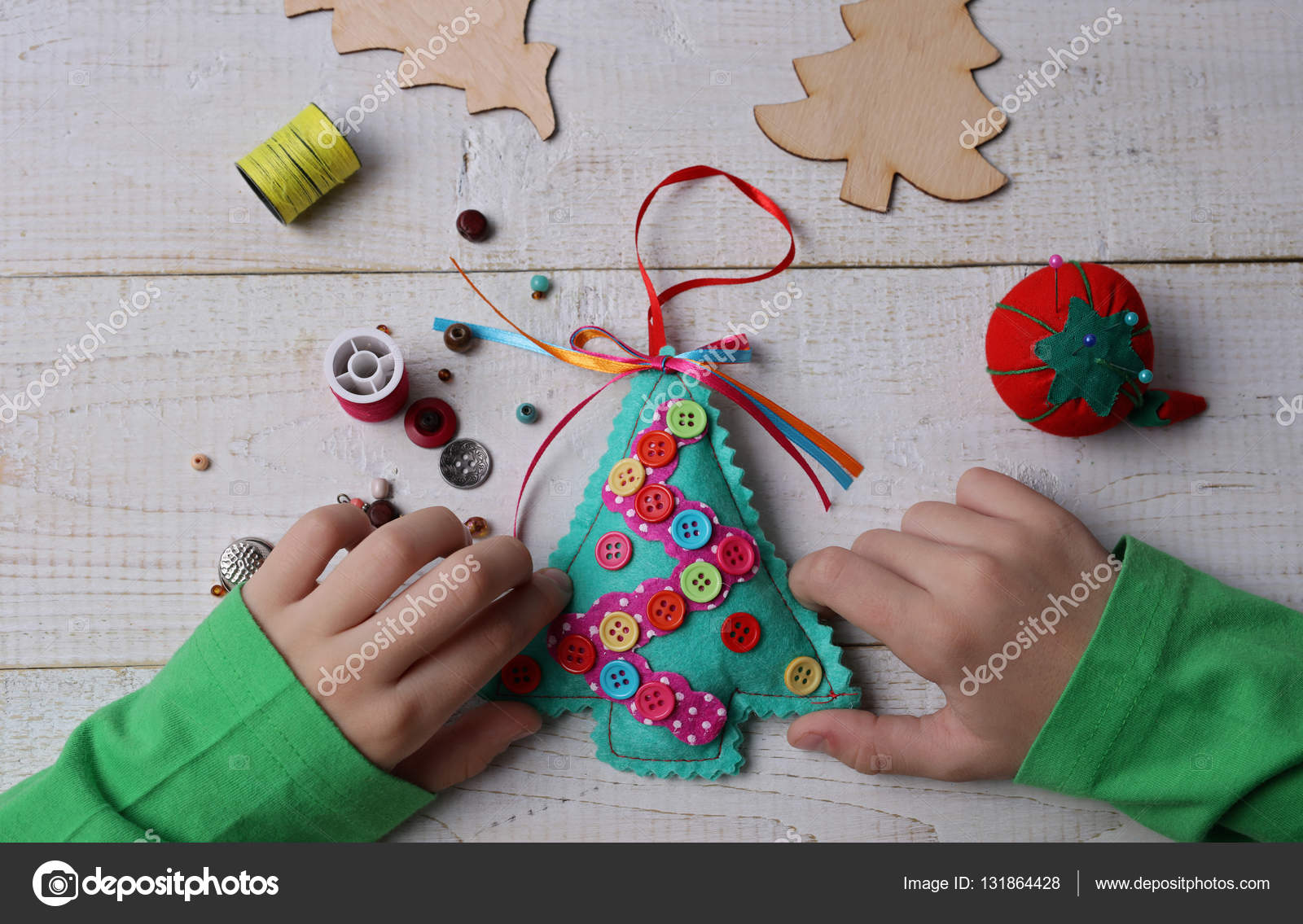 Child making felt Christmas Tree decoration ornament close up Kids Art Art Projects Handmade New Year decorations Happy family concept