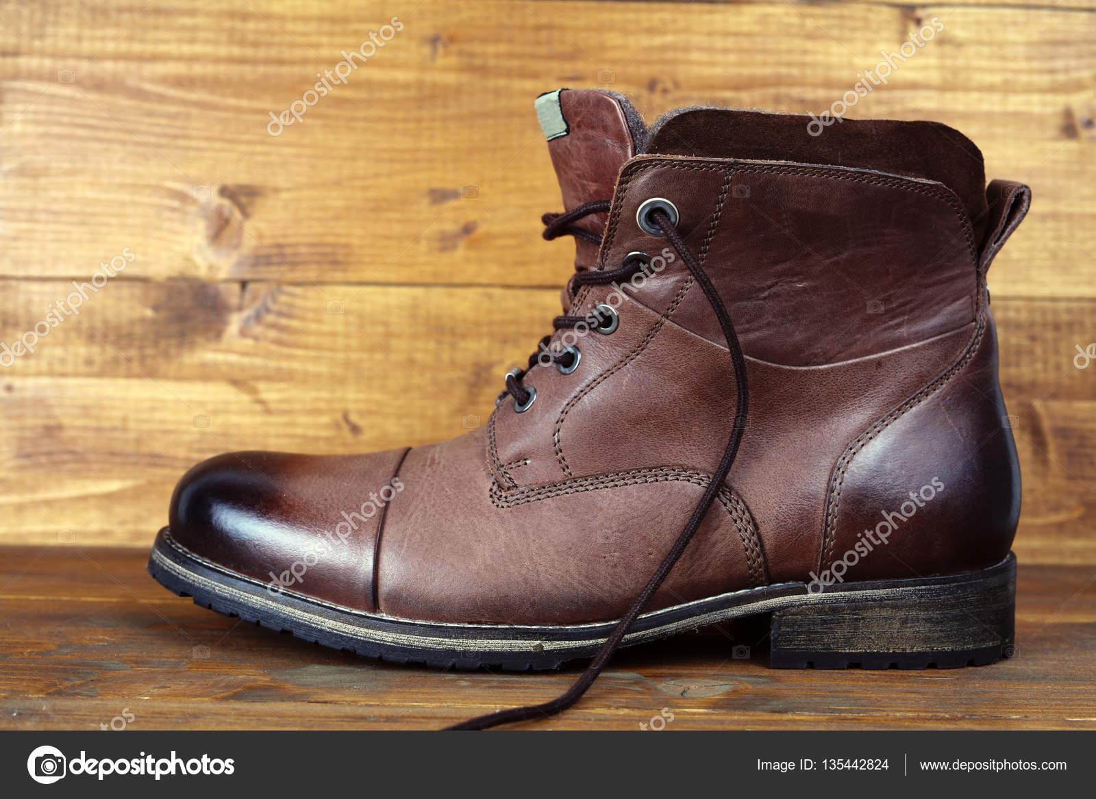 644631f0 Brązowe skórzane zimowe wysokie buty męskie, buty na vintage drewniane tła–  obraz stockowy