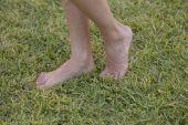 Fiatal lány mezítláb, élvezi a pihenésre a friss zöld fű, szabadban, napos park tavaszi séta. Barefootism