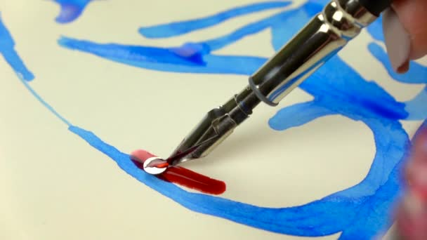 Slow-mo footage. Artist girl hand draws a pen with red ink. close-up