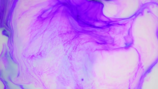 Ink in water. Purple ink reacting in water creating abstract background.