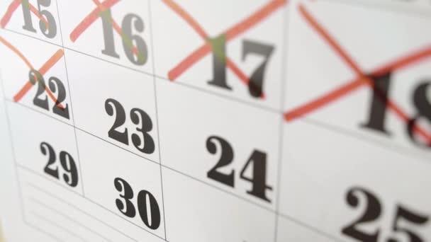 Samičí ruka kříží s červenou značkou v kalendářní den23. Zpomalený výstřel. Zavřít