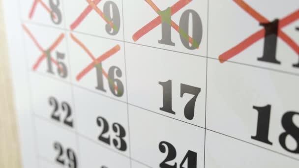 Samičí ruka kříží s červenou značkou v kalendářní den17. Zpomalený výstřel. Zavřít
