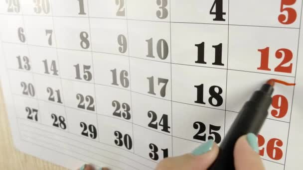 Female hand encircles with red marker the calendar week. Slow motion shot. Close up