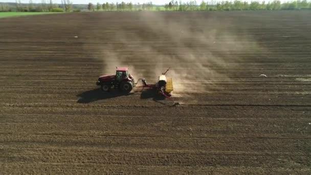 Vitachiv, Ukrajina - 23. dubna 2020: Letecký pohled na traktor pracující na poli s moderním secím strojem na nově oraném poli. Mechanizace výsadby semen.