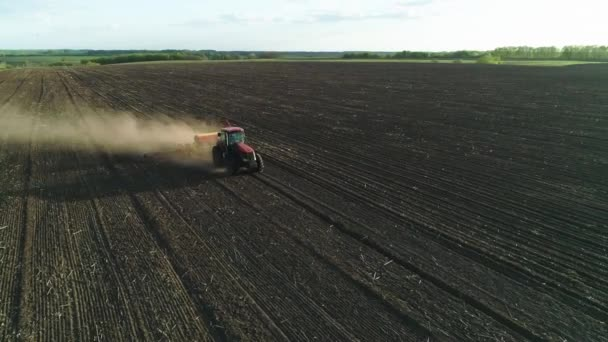 Aerial view of tractor working in the field with a modern sowing seeds machine in a newly plowed field. Planting seeds mechanization. April 27, 2020 Vitachiv, Ukraine