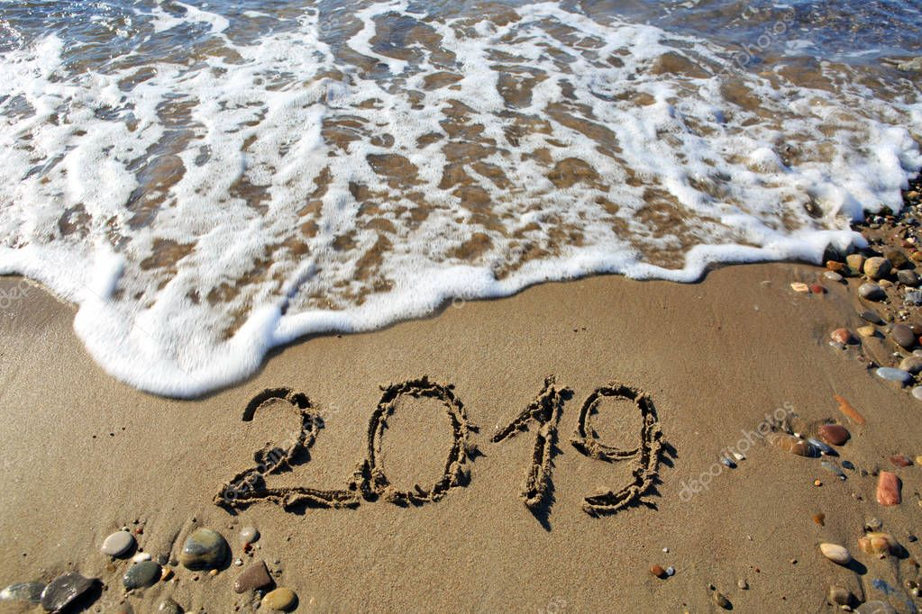 New year 2019 written in sand.