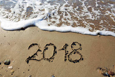 New year 2018 written in sand.