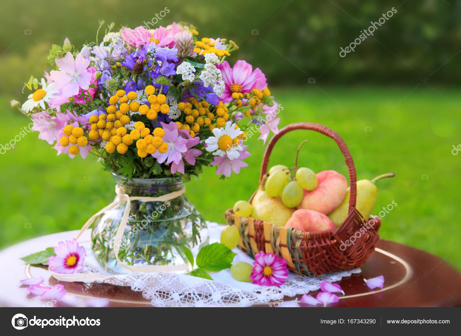 Bouquet des fleurs sauvages colorées et corbeille de fruits. — Photographie swkunst © #167343290