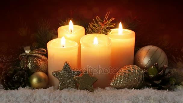 Weihnachtsdekoration und vier brennende Adventskerzen.