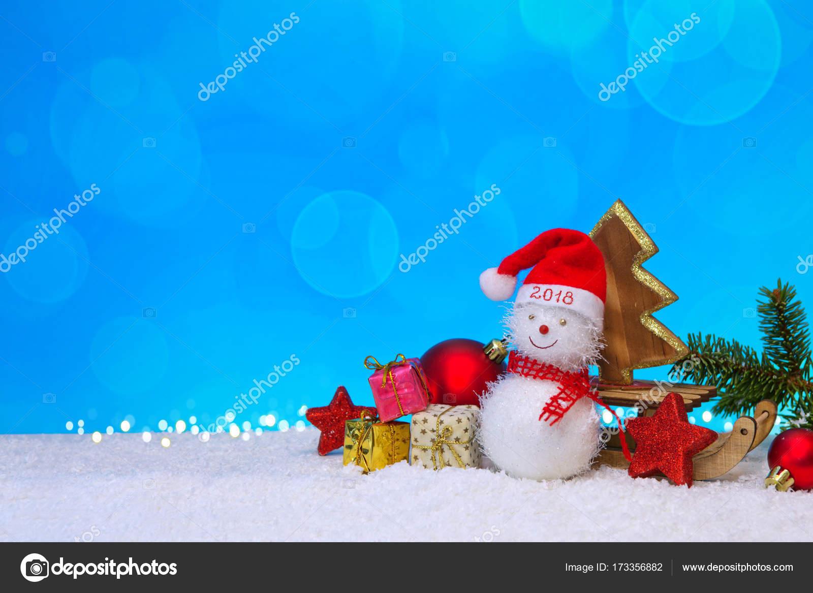 Schneemann mit Weihnachtsgeschenke auf dem Schlitten auf blaue ...