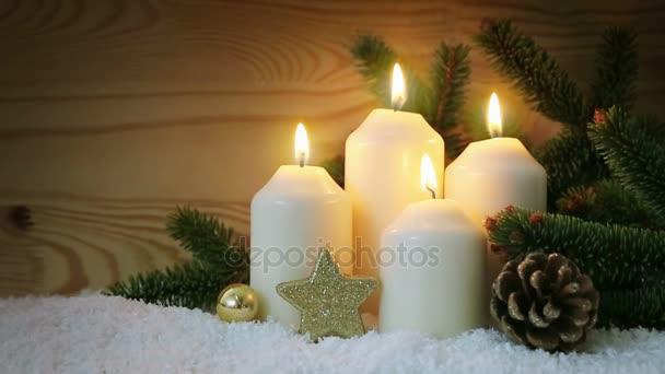 Vánoční dekorace a čtyři hořící adventní svíčky.