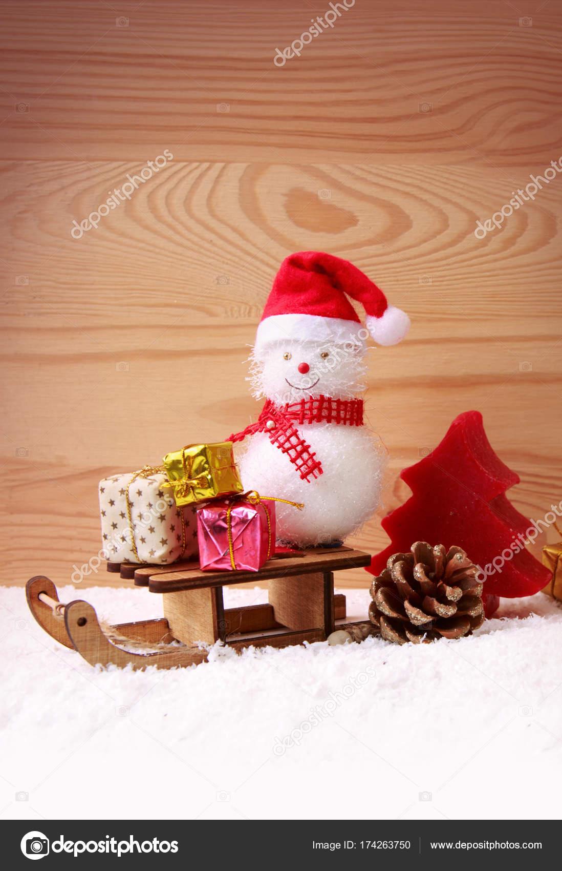 Schneemann mit Weihnachtsgeschenke auf dem Schlitten auf Holz ...