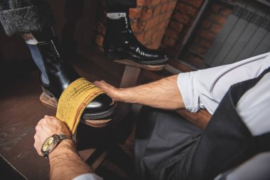 hands of shoemaker working with footwear