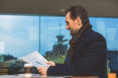 Middle-aged businessman reading newspaper in cafe