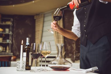 Waiter pouring scarlet wine into glass