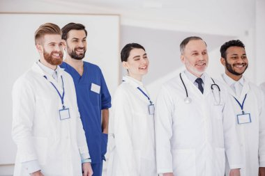 Smiling medical advisers locating in room