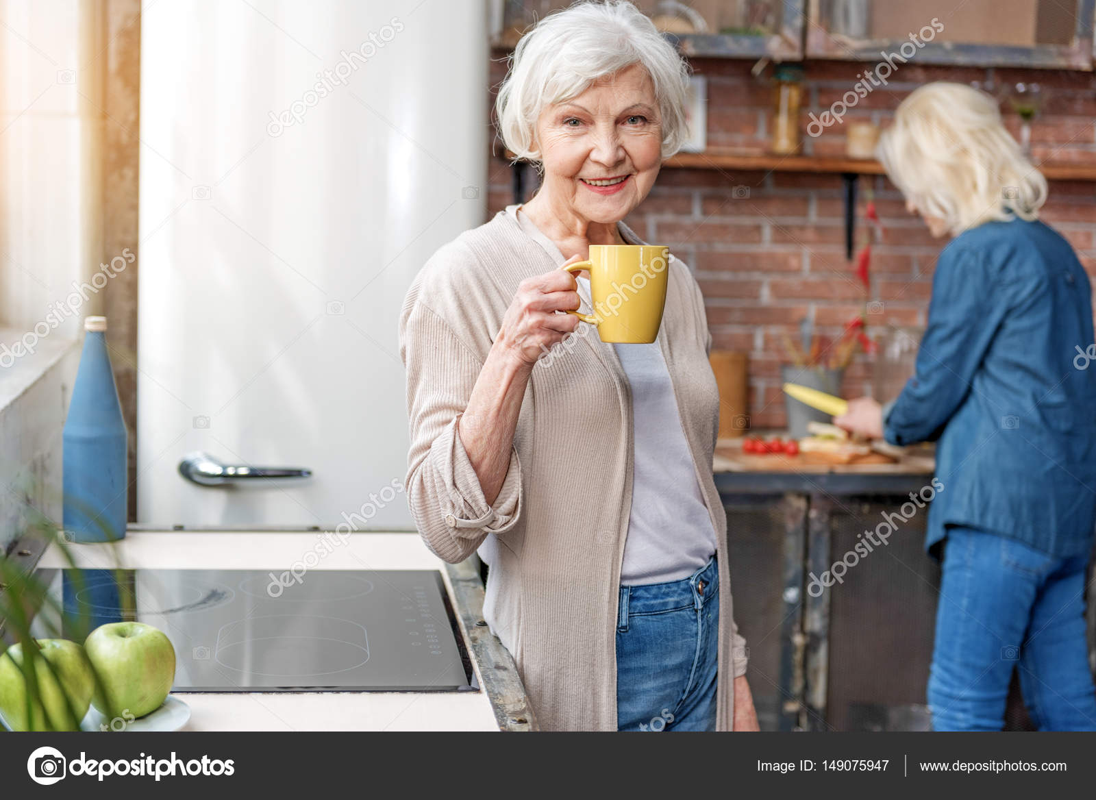 cheerful old lady enjoying hot beverage in kitchen — stock photo