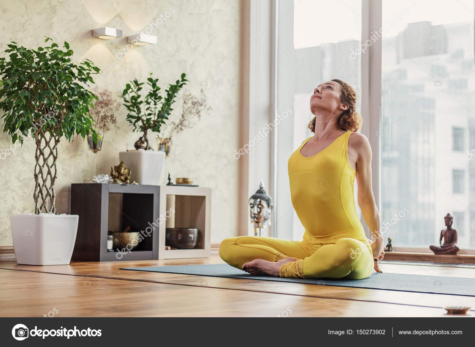 Fit junge frau beim yoga in wohnung stockfoto for Yoga wohnzimmer langenzersdorf